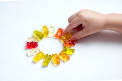 Children's vitamins in the form of bears are arranged in rows.  A lot of multi-colored jelly sweets for children.  The hand of the child reaches and takes a vitamin or candy