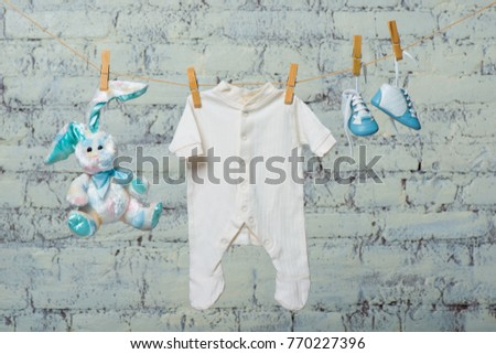 Children's white bodik, boots, panties and a toy rabbit dry on a rope against a white brick wall. #770227396
