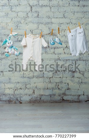 Children's white bodik, boots, panties and a toy rabbit dry on a rope against a white brick wall. #770227399