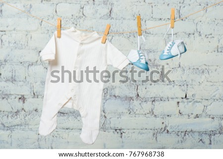 Children's white body and blue shoes on a rope against a white brick wall. #767968738
