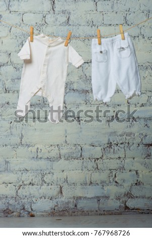 Children's white body and pantyhose dry on a rope against a white brick wall. #767968726
