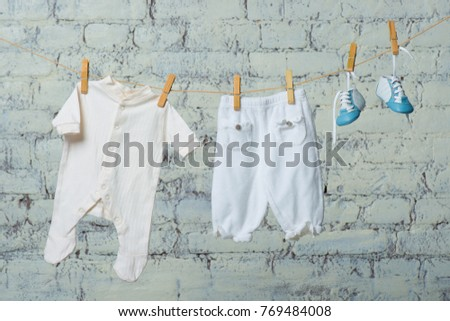 Children's white body, boots and pantyhose dry on a rope against a white brick wall. #769484008