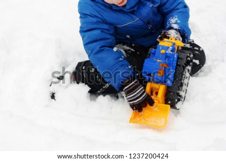 Children's winter games outdoors. The image of the child , who sits on the white snow and playing with a toy excavator.