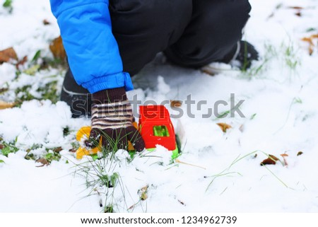 Children's winter games. The child sits among the first snow and plays with a red toy construction equipment. Visible hand, dressed in a blue jacket, black pants and boots.
