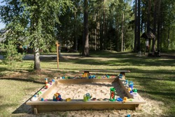 Children sand box in Aegviidu village. Plastic toys spread around the playground, sunbeams giving color to the beige sand. Park of birch and pine trees in the background. Estonia, European Union.