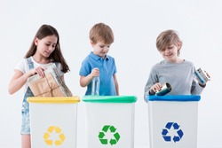 Children segregating paper, glass and metal into yellow, green and blue bins