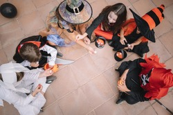 Children sharing and comparing their candies on halloween siting on a floor
