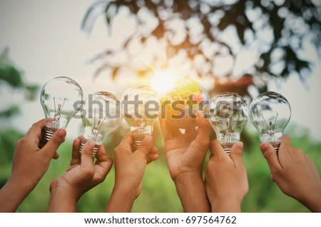 Shutterstock children show hand with light bulb and world toy concept solar energy