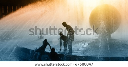 Children silhouettes playing in water fountain at sunset