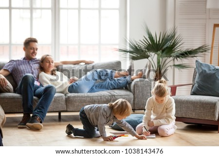 Children sister and brother playing drawing together on floor while young parents relaxing at home on sofa, little boy girl having fun, friendship between siblings, family leisure time in living room #1038143476
