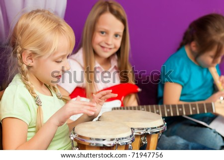 Children � sisters - making music; they are practicing playing guitar, bongo and flute