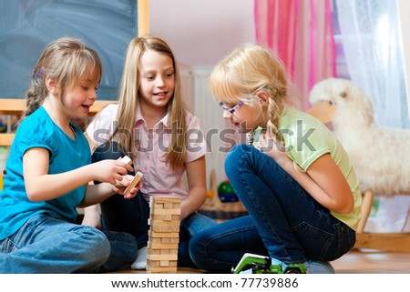 Children - sisters - playing at home with bricks
