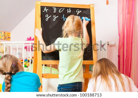 Children - sisters - playing school in their room
