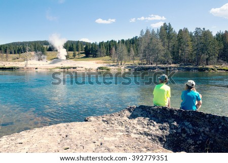 Children sit near the Yellowstone River and look at the steaming geysers. Yellowstone National Park, US