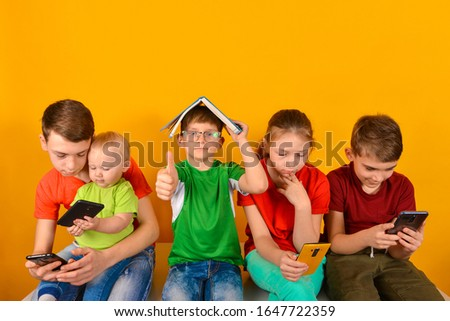 Children sit next to each other and look at the phone, while one boy in glasses sits with a book. The concept of online learning at home