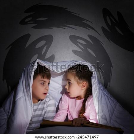 Children sitting in bed under blanket with book