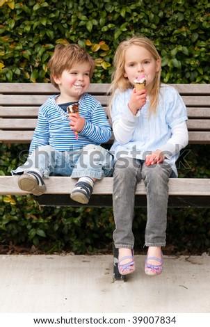 Children sitting in park eating ice-cream
