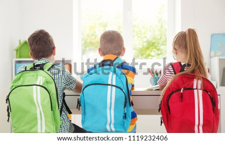 Children sitting in the room with books and backpacks. Pupils reading at school