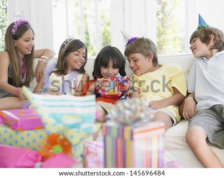 Children sitting on sofa at birthday party as one open the gift