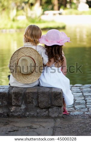 Children sitting on the bank of lake in park
