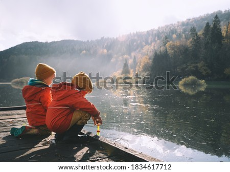 Children spend time outside in fresh and cold air. Small kids play in nature. Healthy childhood. Family life background. Siblings playing near by water in park outdoors. Little friends in countryside. ストックフォト ©