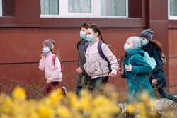 Children students in medical masks leave the school