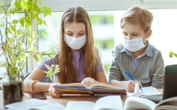Children study at home in a protective face mask during Quarantine CoVid-19, distance learning online with a laptop, a boy and a girl do their homework for school. Schoolchildren stayed at home.