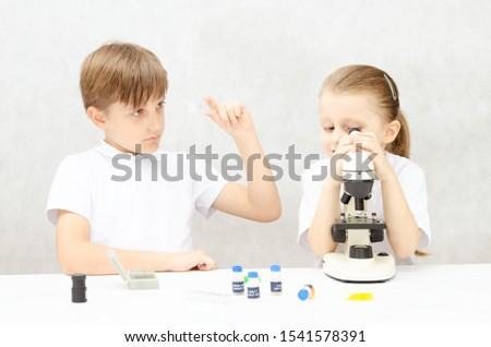 Children study biology and microorganisms. A girl looks through a microscope, a little boy looks at biological samples.