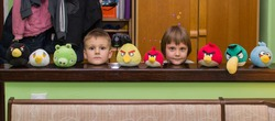 Children surrounded by stuffed toys