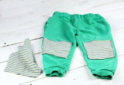 Children sweatpants mended with patches.  Patch with stripes on blue worn sweatsuit.