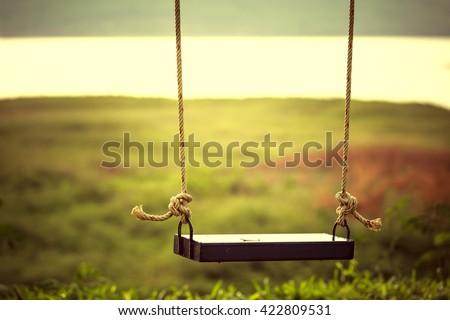 Children swing in the park (vintage tone)