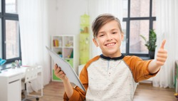 children, technology and people concept - smiling boy with tablet pc computer showing thumbs up at home over children's room background