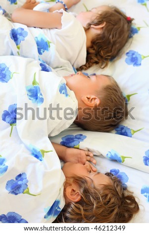 children three together sleeping on bed in cozy room