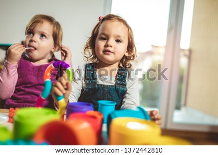 Children toddlers girls play toys at home, kindergarten or nursery.