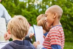 Children together make a field game or a treasure hunt in kindergarten