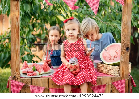 Children trying to sell lemonade. Watermelon lemonade with ice and mint as summer refreshing drink in jars. Cold soft drinks with fruit. Children boy and girls drinking lemonade in jar