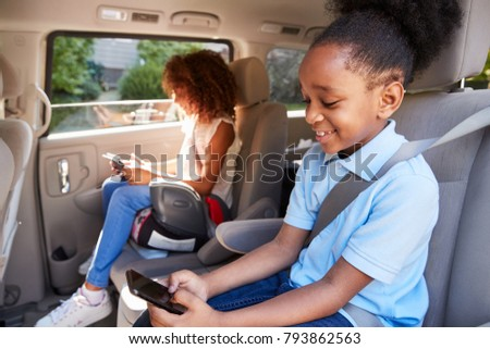 Children Using Digital Devices On Car Journey