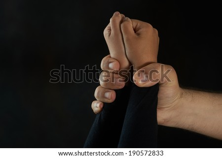 Children violence. Man\'s hand holding tight girl\'s hands