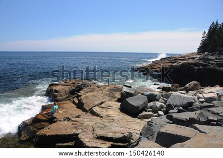 Children waiting on waves to hit the rocky coast of Maine at Schoodic Point