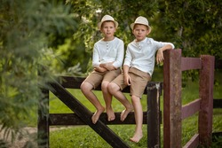 Children walk in the park. Twins are sitting on a wooden fence. Boys in hats, shirts and shorts. Image with selective focus.