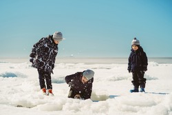 children walking on ice piling of finland gulf. boy slump under ice cake. image with selective focus