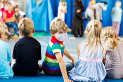 Children watching theater or concert at school. Little kid boy wear medical mask as protection from corona virus on covid quarantine. Kids from back, musical and theatrical performace