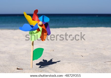 Children windmill on a sandy beach on the ocean