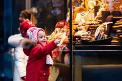 Children window shopping on traditional Christmas market in Germany on snowy winter day. Kids buying candy, pastry and gingerbread in confectionery. Boy and girl choosing sweets in Xmas bakery.