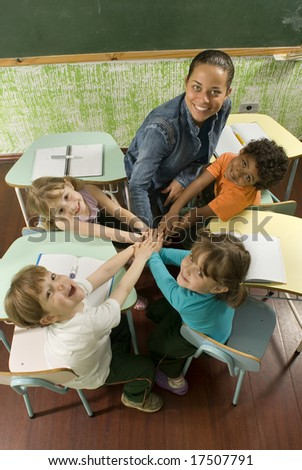 Children with a teacher in a classroom.  Their hands are clasped as a group.  They are facing the camera and are smiling. Vertically framed shot.