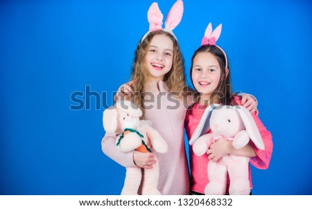 Children with bunny toys on blue background. Sisters smiling cute bunny costumes. Spread joy and happiness around. Hope love and joyful living. Friends little girls with bunny ears celebrate Easter. #1320468332