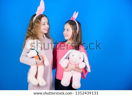 Children with bunny toys on blue background. Sisters smiling cute bunny costumes. Spread joy and happiness around. Friends little girls with bunny ears celebrate Easter. Hope love and joyful living. #1352439131