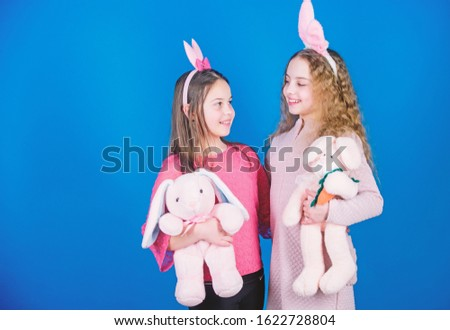 Children with bunny toys on blue background. Sisters smiling cute bunny costumes. Spread joy and happiness around. Friends little girls with bunny ears celebrate Easter. Hope love and joyful living.