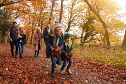 Children With Handful Of Leaves As Multi-Generation Family Walking Along Autumn Woodland Path
