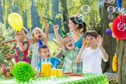 Children with party hats and trumpets during garden party